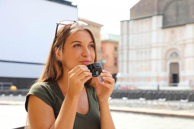 Ritratto di bella donna sorridente che si siede nel caffè all'aperto in italia, bevendo caffè