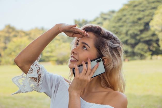 Ritratto di una bella donna sorridente che manda messaggi e parla con il suo telefono