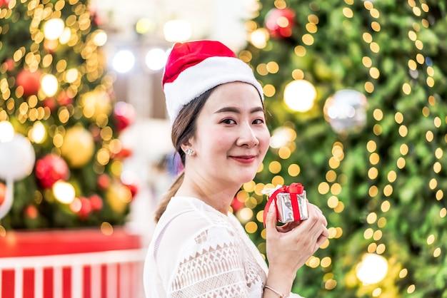 Ritratto di sorridente bella giovane donna asiatica con regalo sulla festa di natale in fiera