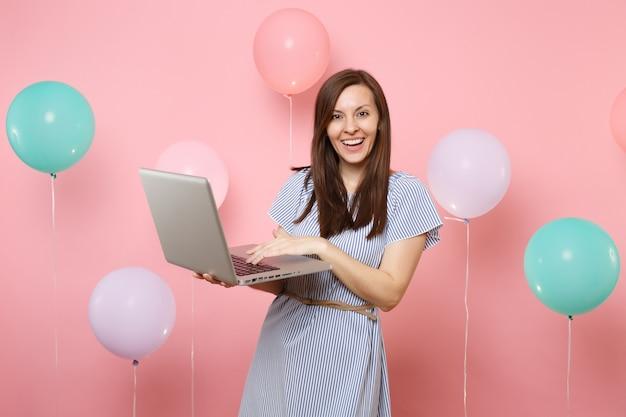 Ritratto di bella giovane donna sorridente in vestito blu che tiene utilizzando il computer pc portatile su sfondo rosa pastello con mongolfiere colorate. festa di compleanno, concetto di emozioni sincere della gente.