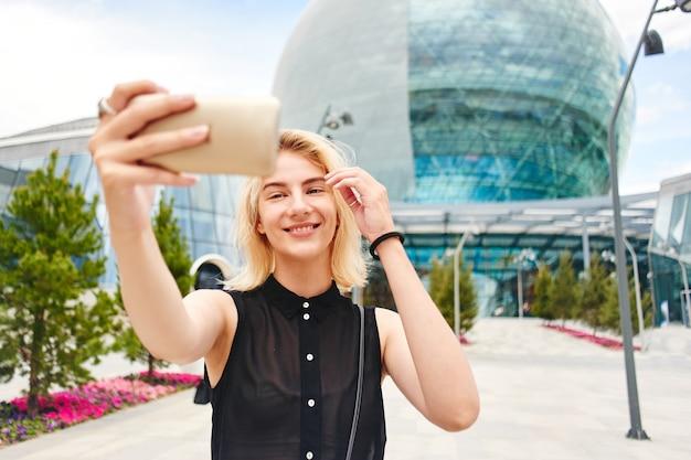 Il ritratto di una ragazza bionda sorridente nel nero fa la foto del selfie sul cellulare sullo sfondo di un edificio commerciale di vetro