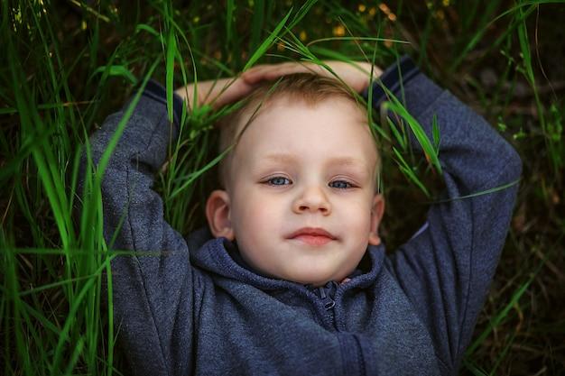 Ritratto di un ragazzino biondo sorridente sdraiato sull'erba verde