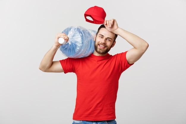 Ritratto del corriere di consegna dell'acqua in bottiglia sorridente in maglietta rossa e nel carro armato di trasporto del cappuccio di