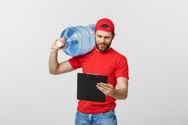 Corriere sorridente di consegna dell'acqua in bottiglia del ritratto in maglietta e cappuccio rossi