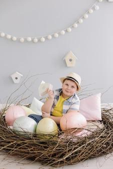 Ritratto di un ragazzo sorridente in un cappello nel nido decorativo di pasqua con le uova di pasqua, rami di salice secco.