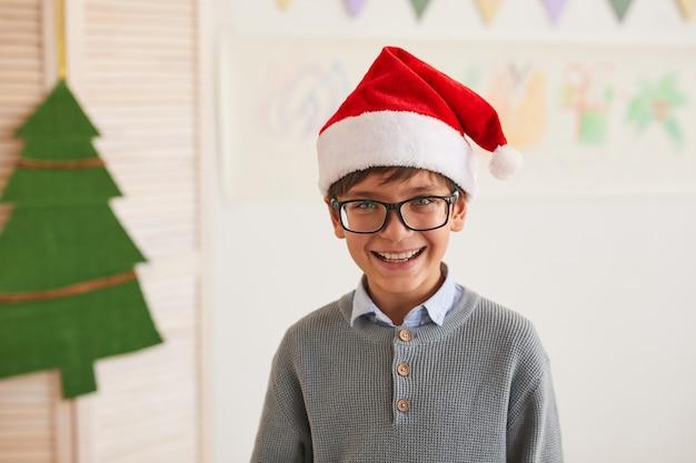Ritratto del ragazzo sorridente che porta il cappello della santa e che guarda l'obbiettivo mentre gode del corso di arte su natale, spazio della copia