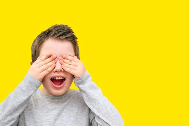 Ritratto di un ragazzo sorridente con gli occhi chiusi con i palmi delle mani, bocca aperta Foto Premium