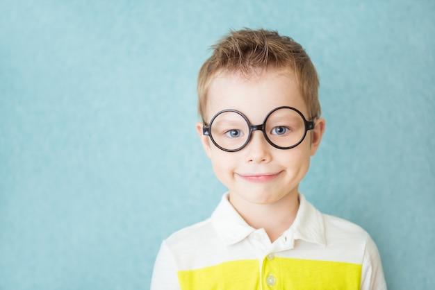 Ritratto di un ragazzo sorridente con gli occhiali sul blu
