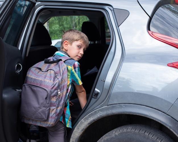 Ritratto del ragazzo sorridente con la borsa di scuola che perde nell'automobile. portare un allievo dopo la scuola. il ragazzo sale in macchina.