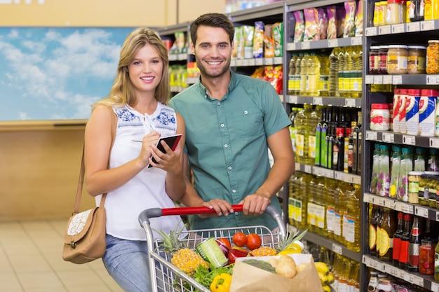 Ritratto delle coppie luminose sorridenti che comprano prodotti alimentari e che utilizzano taccuino