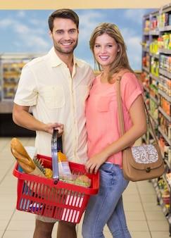 Ritratto delle coppie luminose sorridenti che comprano prodotti alimentari facendo uso del cestino della spesa