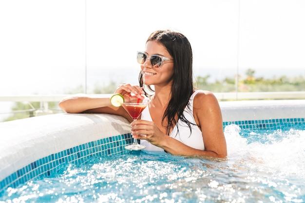 Ritratto di donna bruna sorridente in costume da bagno bianco e occhiali da sole, prendere il sole e bere cocktail in piscina durante le vacanze