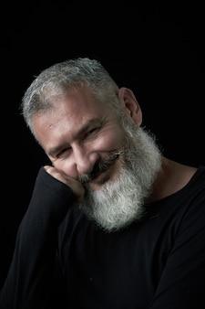 Ritratto di un uomo dai capelli grigi brutale sorridente con una barba lussureggiante dai capelli grigi su sfondo nero, messa a fuoco selettiva