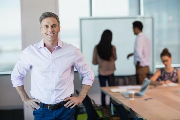 Ritratto di sorridente dirigente aziendale in piedi con le mani sui fianchi in sala conferenze
