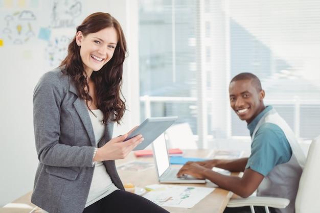 Ritratto della gente di affari sorridente che utilizza compressa digitale e computer portatile