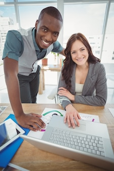 Ritratto dei professionisti sorridenti di affari che per mezzo del computer portatile