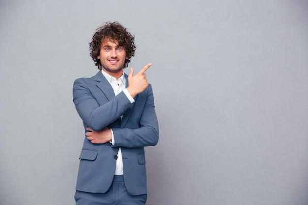 Ritratto di un uomo d'affari sorridente che punta il dito lontano oltre il muro grigio e guardando la parte anteriore
