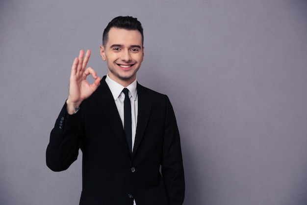 Ritratto di un uomo d'affari sorridente che mostra il segno ok sul muro grigio