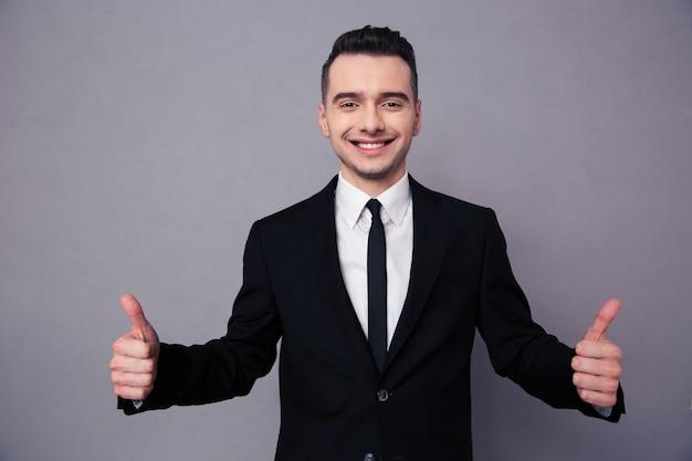 Ritratto di un uomo d'affari sorridente che mostra i pollici in su sul muro grigio gray