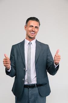 Ritratto di un uomo d'affari sorridente che mostra i pollici in su isolato