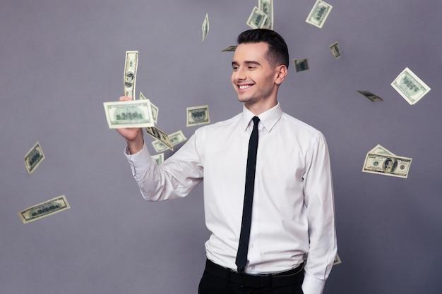 Ritratto di un uomo d'affari sorridente in piedi sotto la pioggia con soldi su un muro grigio