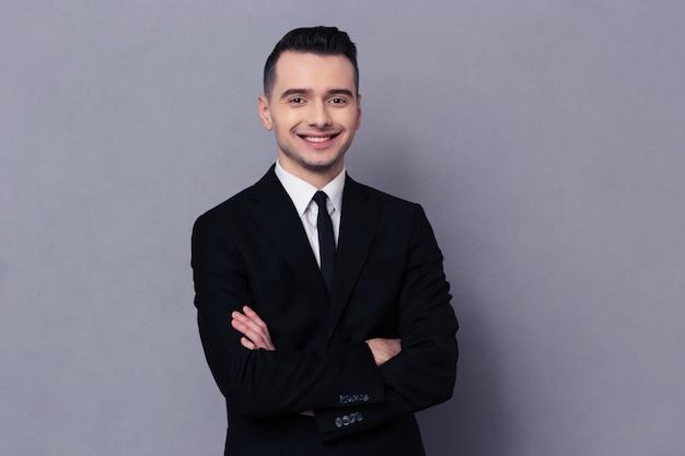 Ritratto di un uomo d'affari sorridente in piedi con le braccia piegate sul muro grigio e