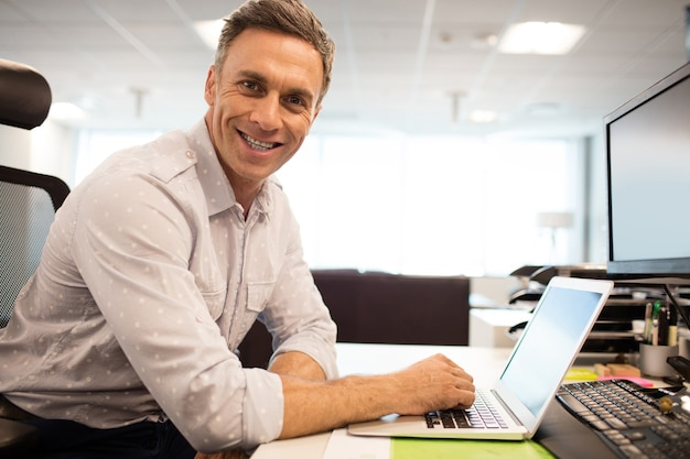 Ritratto di uomo d'affari sorridente utilizzando laptop mentre era seduto in ufficio