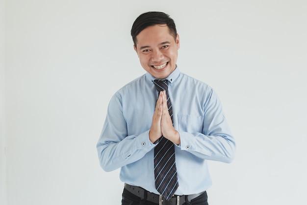 Ritratto di uomo d'affari sorridente che indossa camicia blu e cravatta che saluta alla telecamera