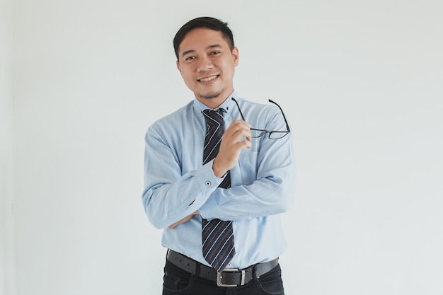 Ritratto di uomo d'affari sorridente che indossa camicia blu e cravatta con gli occhiali in telecamera