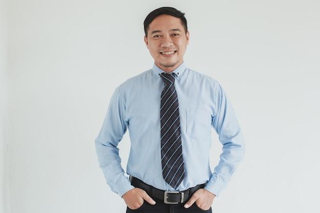Ritratto di uomo d'affari sorridente che indossa camicia blu e cravatta in posa con fiducia su sfondo bianco