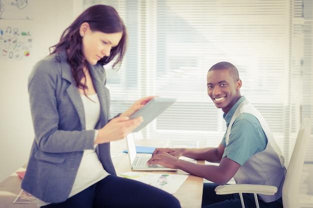 Ritratto dell'uomo d'affari sorridente che lavora al computer portatile con la donna che per mezzo della compressa digitale