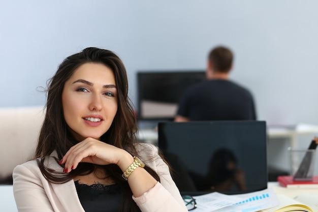 Ritratto di sorridere imprenditrice al suo tavolo di lavoro