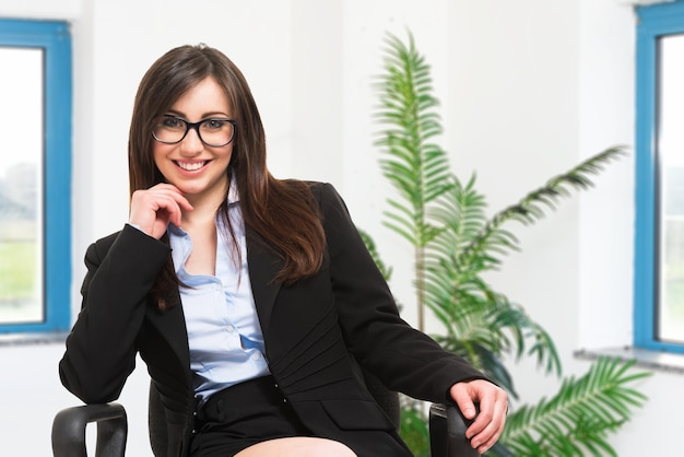 Ritratto di una donna d'affari sorridente seduto su una sedia
