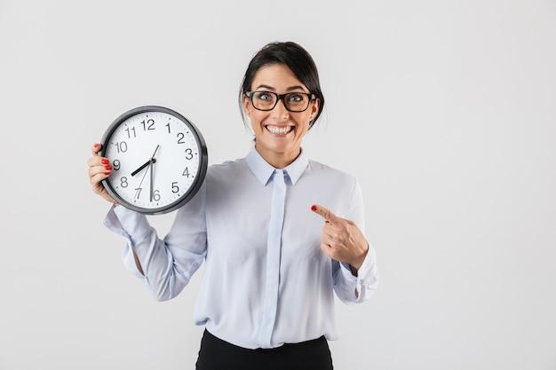 Ritratto di sorridente imprenditrice indossando occhiali da vista azienda orologio rotondo in ufficio, isolato su muro bianco
