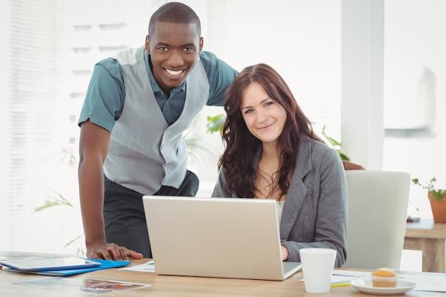 Ritratto della donna di affari sorridente che lavora al computer portatile con il collega allo scrittorio