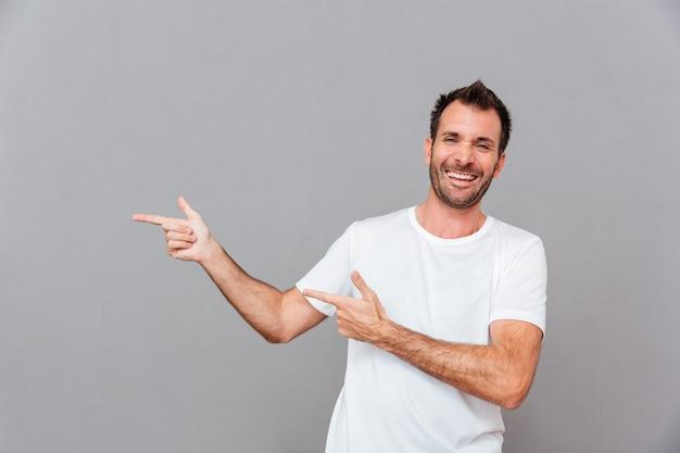 Ritratto di un uomo casual sorridente che punta il dito lontano su sfondo grigio