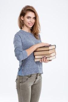Ritratto di una donna casual sorridente che tiene libri isolati su uno sfondo bianco