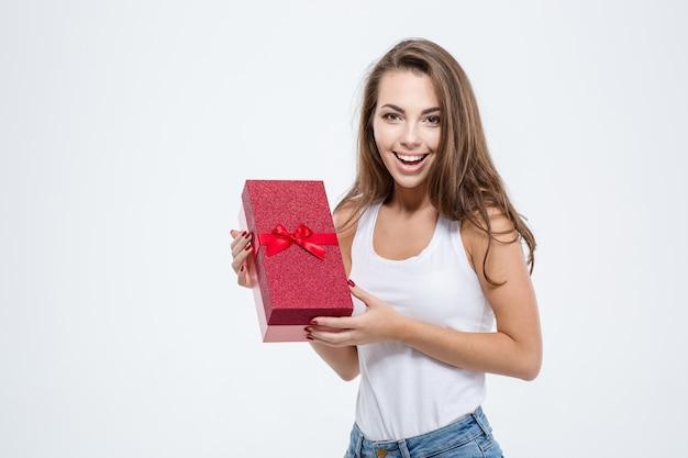 Ritratto di una donna casual sorridente che tiene in mano una confezione regalo isolata su uno sfondo bianco