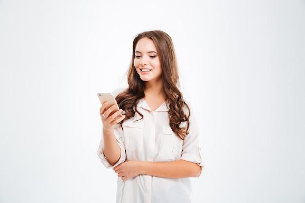 Ritratto di una donna casual sorridente che tiene lo smartphone sul muro bianco