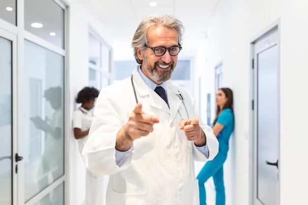 Ritratto del medico maschio caucasico sorridente indossa l'uniforme medica bianca,