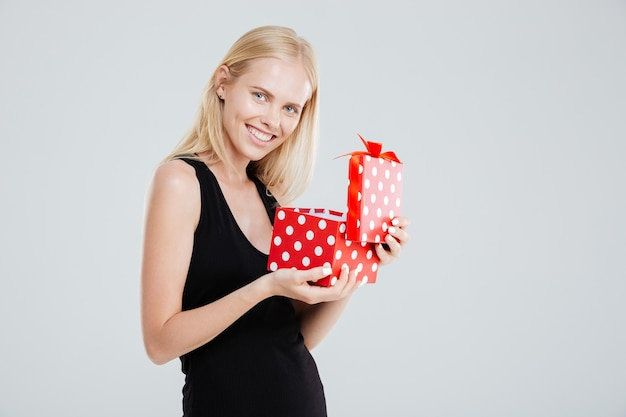Ritratto di una donna allegra sorridente in confezione regalo apertura abito isolato su uno sfondo bianco
