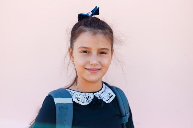 Ritratto di ragazza bambino sorridente su sfondo di colore rosa pastello.