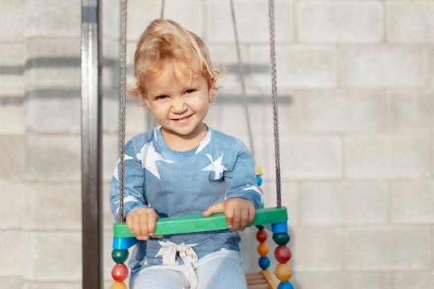 Ritratto della ragazza sorridente del bambino che si siede sulla giostra nel parco giochi all'aperto per bambini.