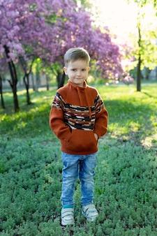 Ritratto di un bambino sorridente (ragazzo felice) sullo sfondo di un albero in fiore in primavera.