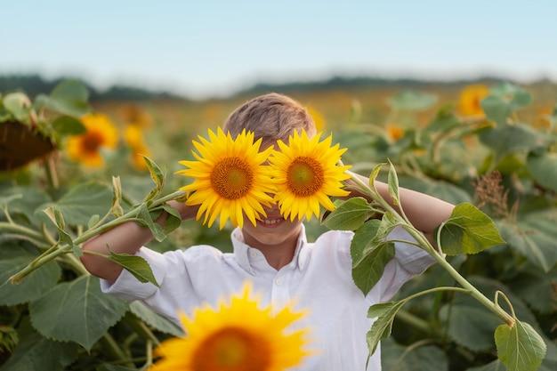 Bambino sorridente del ritratto con il girasole nel giacimento del girasole di estate sul tramonto.
