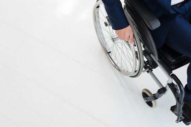 Ritratto dei colleghi sorridenti che stanno dietro l'uomo che si siede sulla sedia a rotelle
