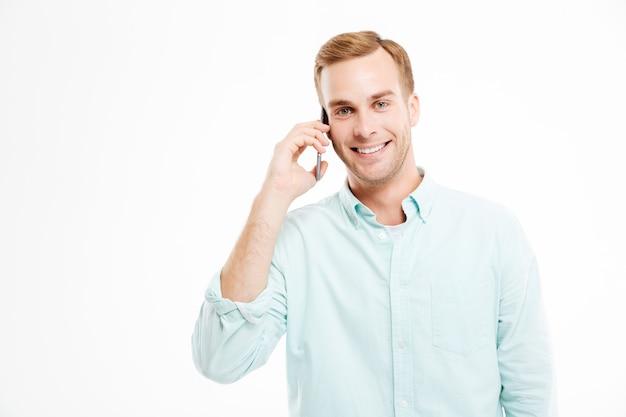 Ritratto di giovane uomo d'affari fiducioso sorridente che parla al telefono cellulare sopra il muro bianco
