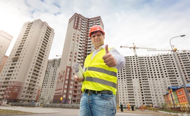Ritratto di ingegnere edile sorridente in piedi al cantiere e tenendo i pollici in su