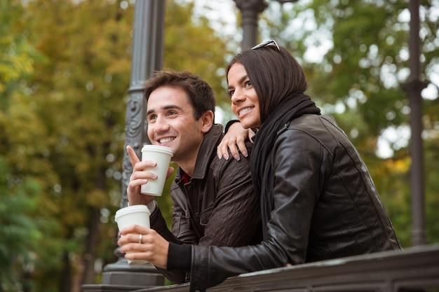 Ritratto di una coppia sorridente con caffè alla ricerca di qualcosa all'aperto