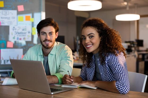 Ritratto di sorridere creativo uomini d'affari con il computer portatile che lavora alla scrivania in ufficio